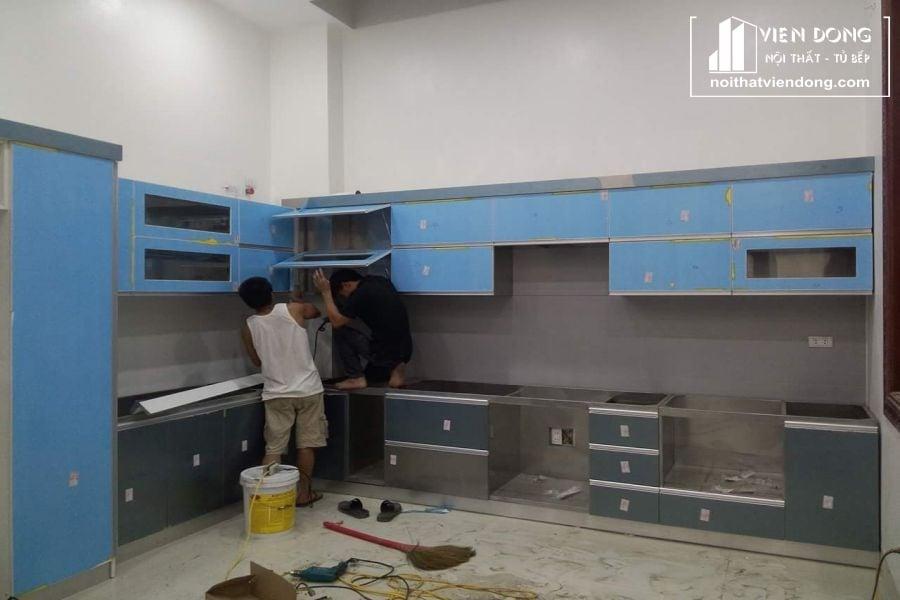 mẫu tủ bếp chữ L với chất liệu thùng inox và cánh acrylic